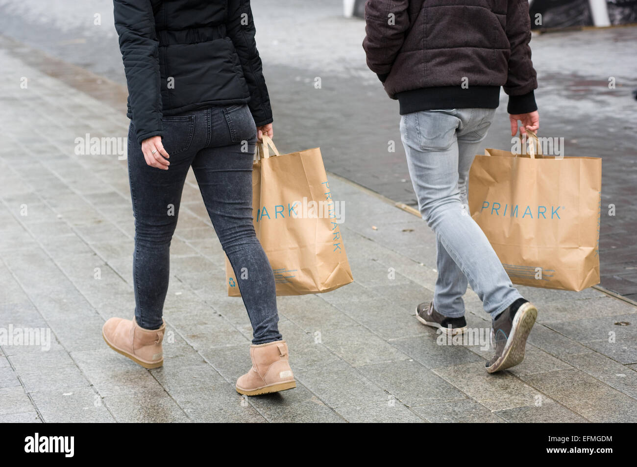 ENSCHEDE, THE NETHERLANDS - 05 FEB, 2015: Twp persons with shopping bags from Primark warehouse are walking on the - Stock Image