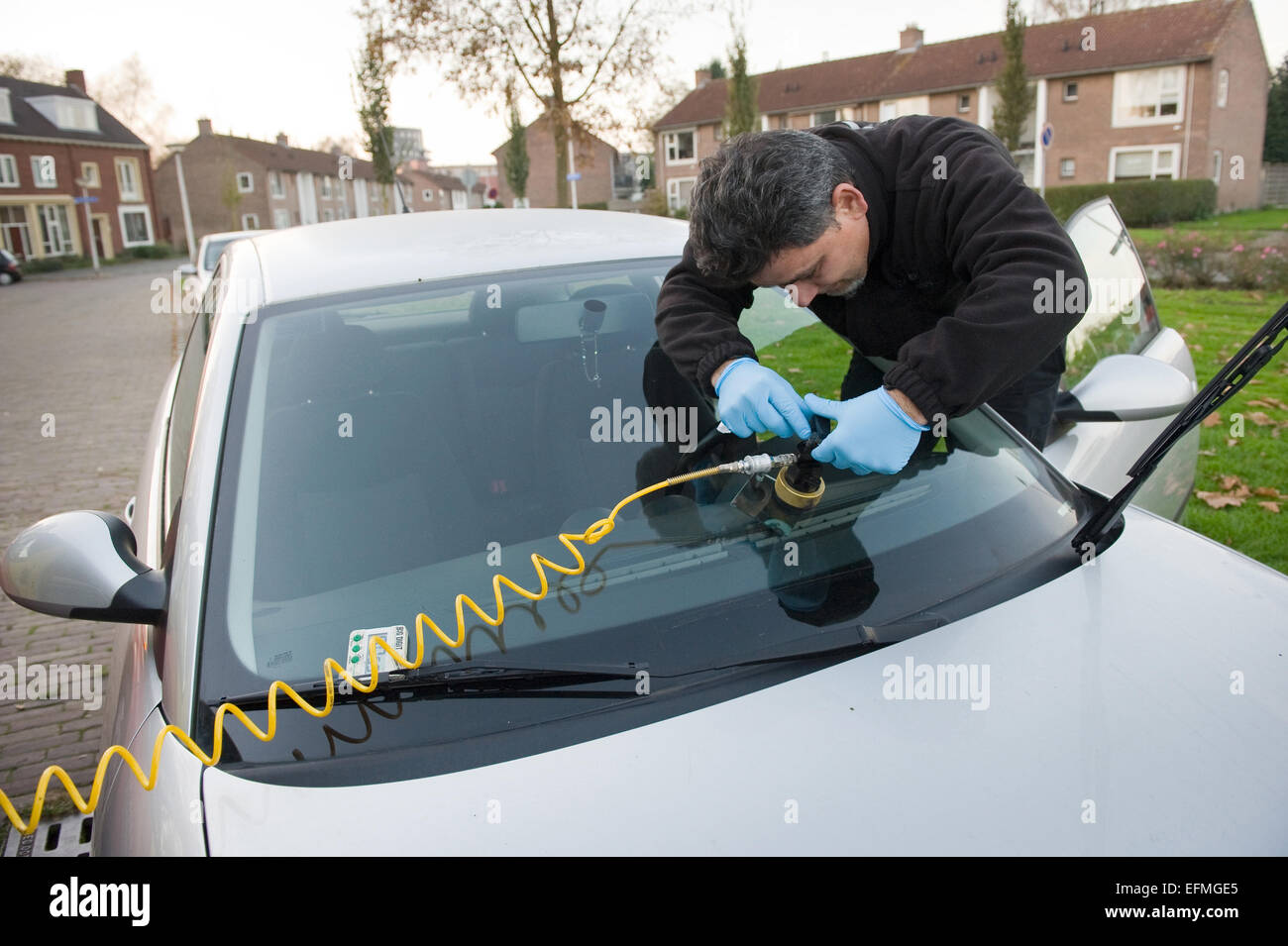 A serviceman from 'carglass' is repairing a crack in the windshield of a car on location - Stock Image