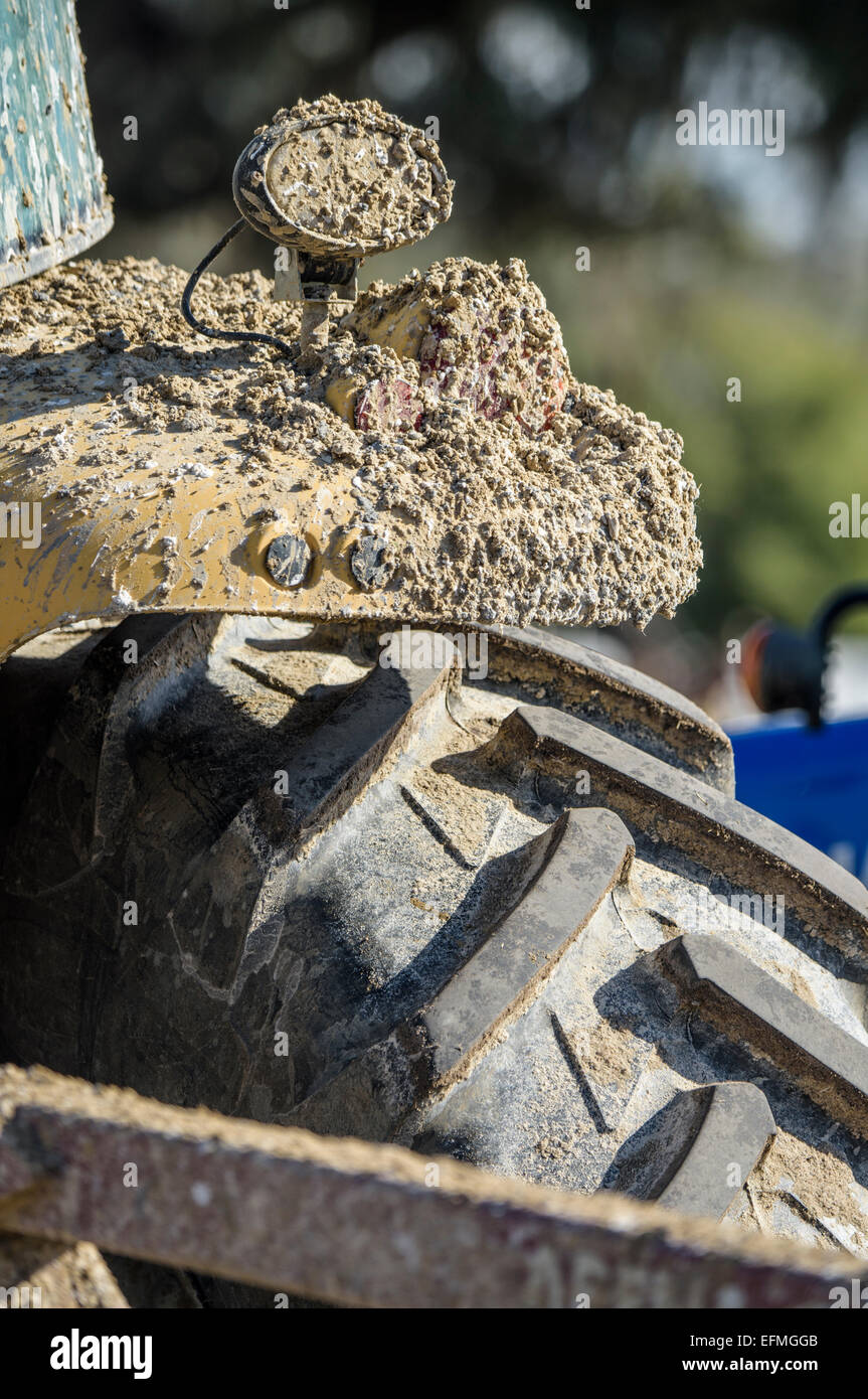 tractor tire and fender covered in mud - Stock Image