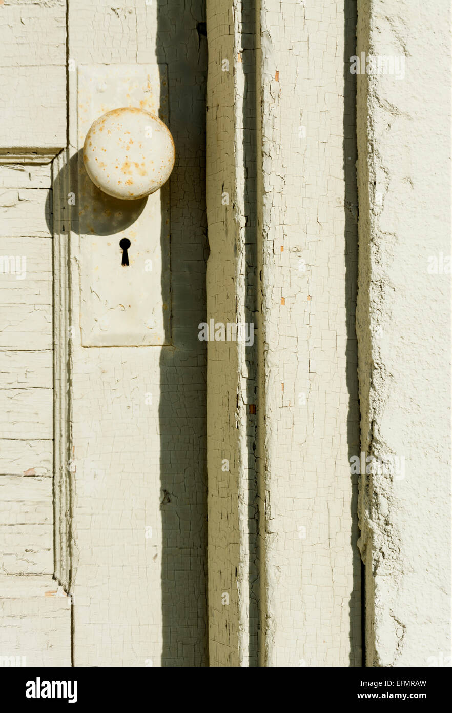 Old antique door knob with cracked paint - Stock Image