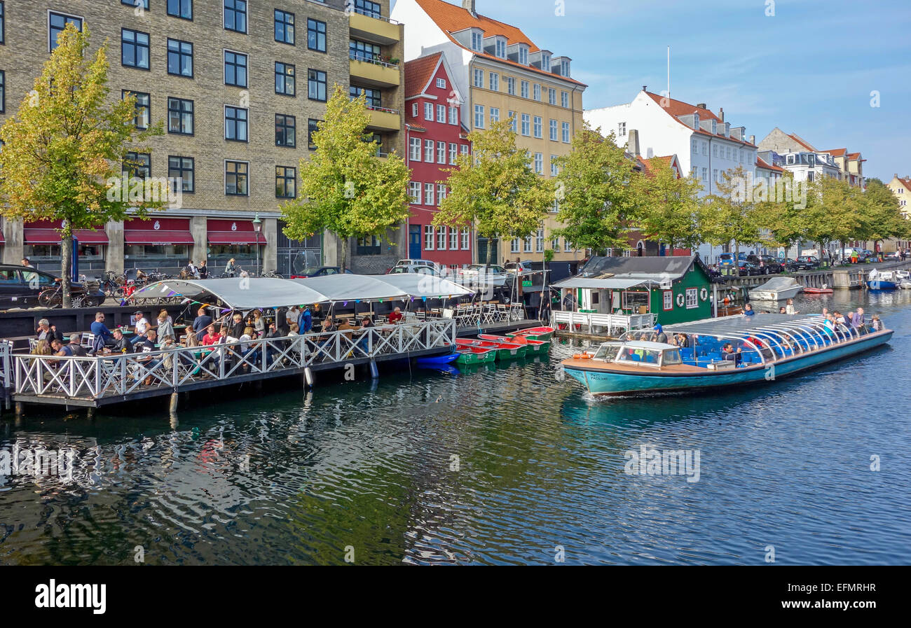 Christianshavn Canal in Copenhagen Denmark with restaurant & vessels along both quays and harbour cruise vessel - Stock Image