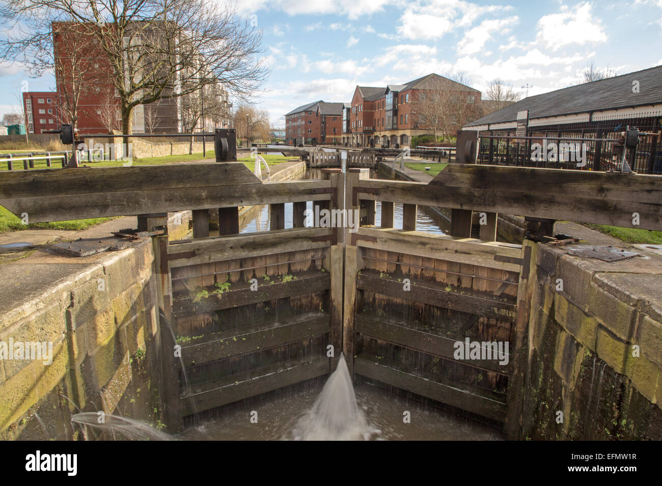 A lock on the Leeds Liverpool canal in the town of Wigan; near Wigan Pier. - Stock Image