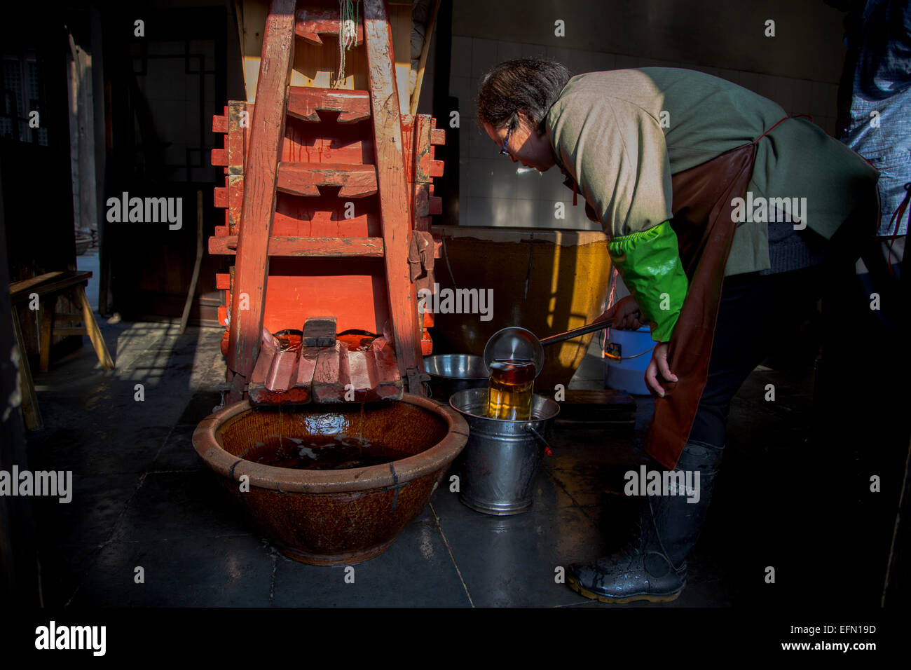 traditional brewing technique of Chinese rice wine: woman is checking the rice wine pressed from fermented mash. - Stock Image