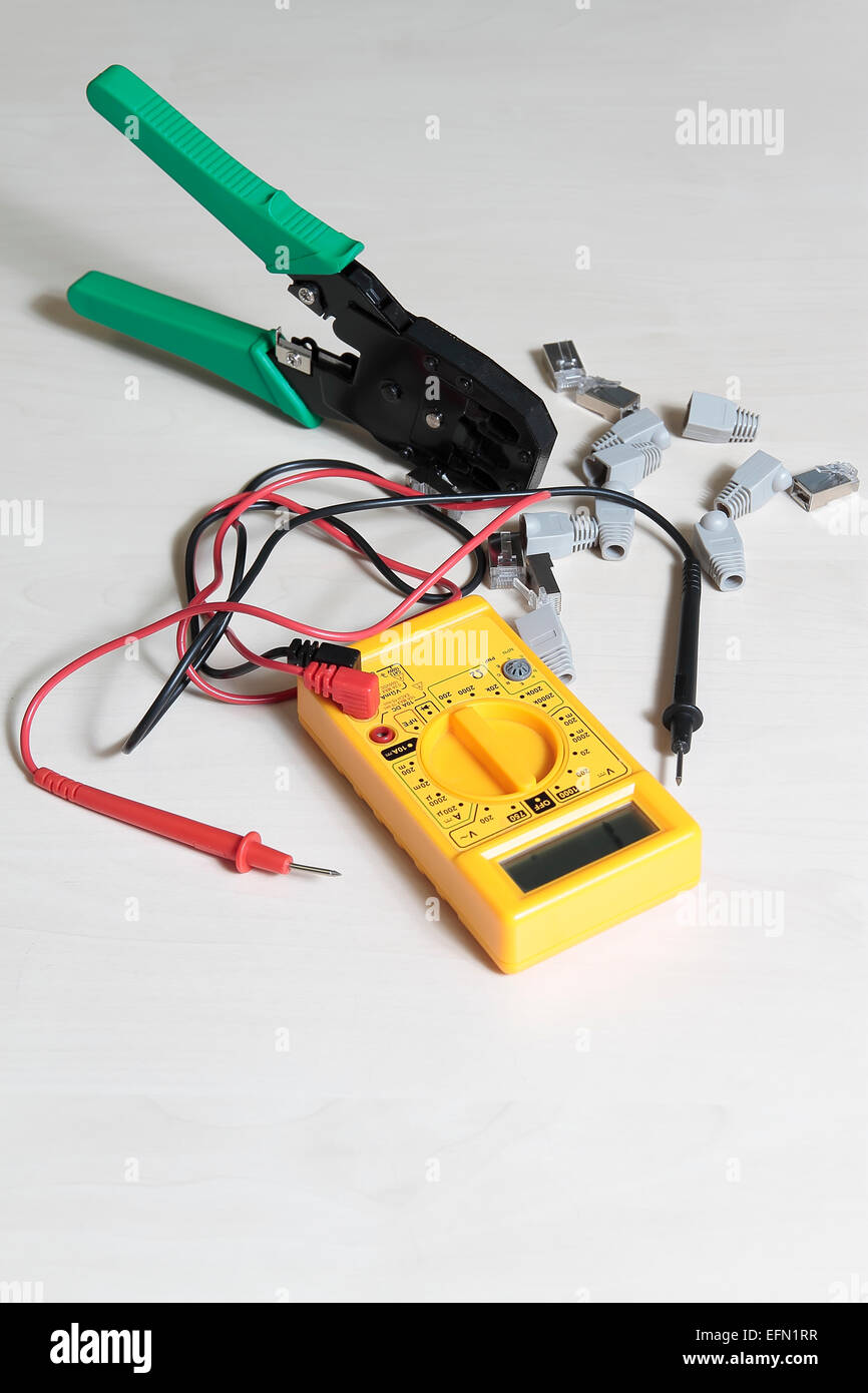 multimeter tester, press pliers and RJ45 connectors - Stock Image