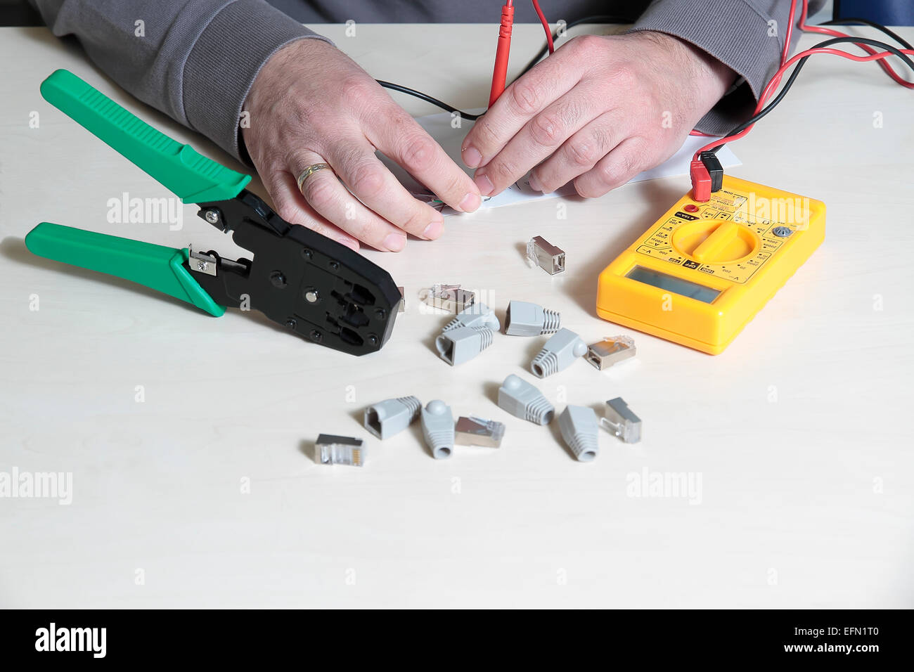 hands using a digital multimeter tester to test a RJ45 connector Stock Photo