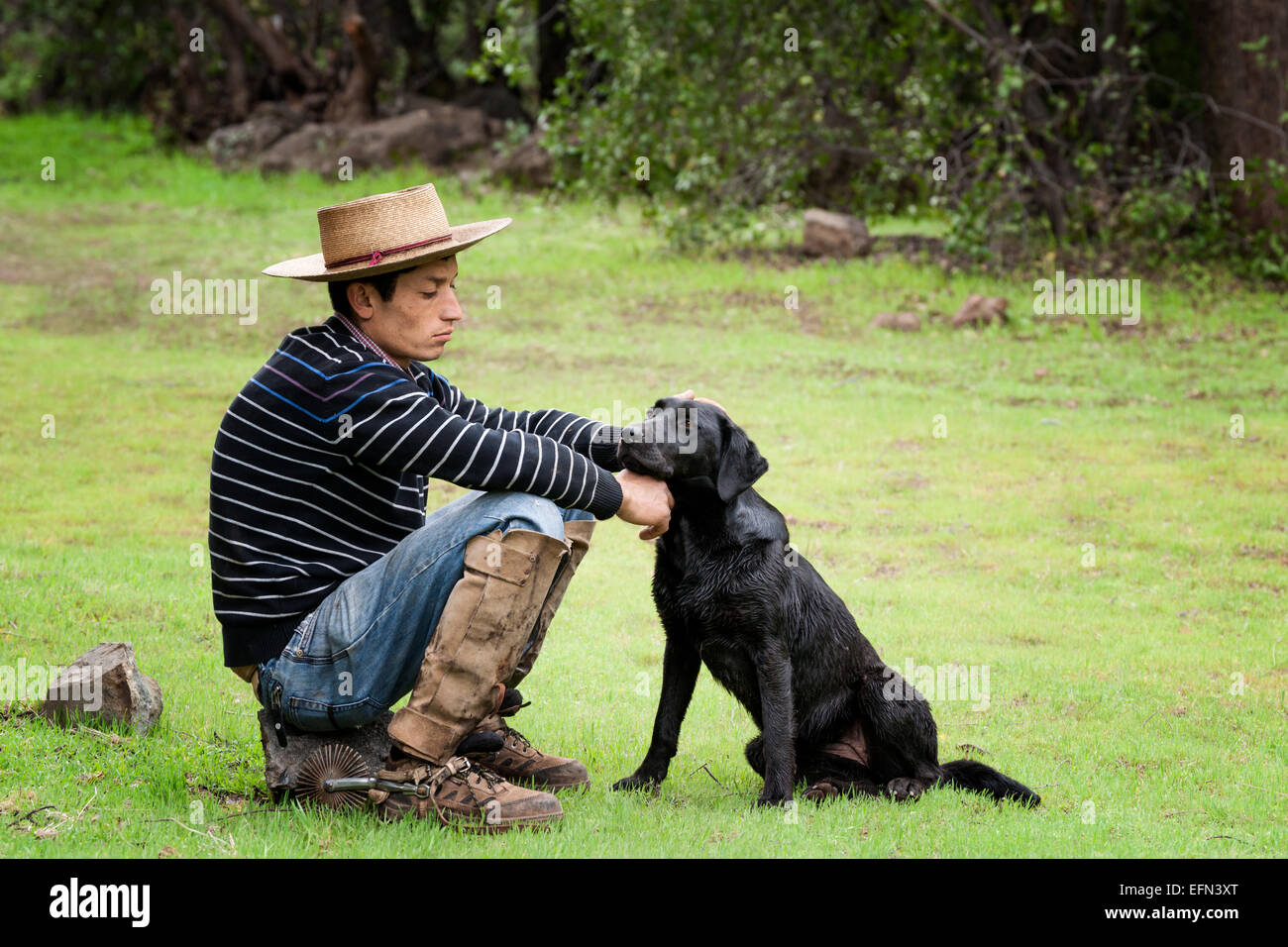 Chilean cowboy (arriero) pets his black dog as sits on a rock in the valley in El Toyo region of Cajon del Maipo, - Stock Image