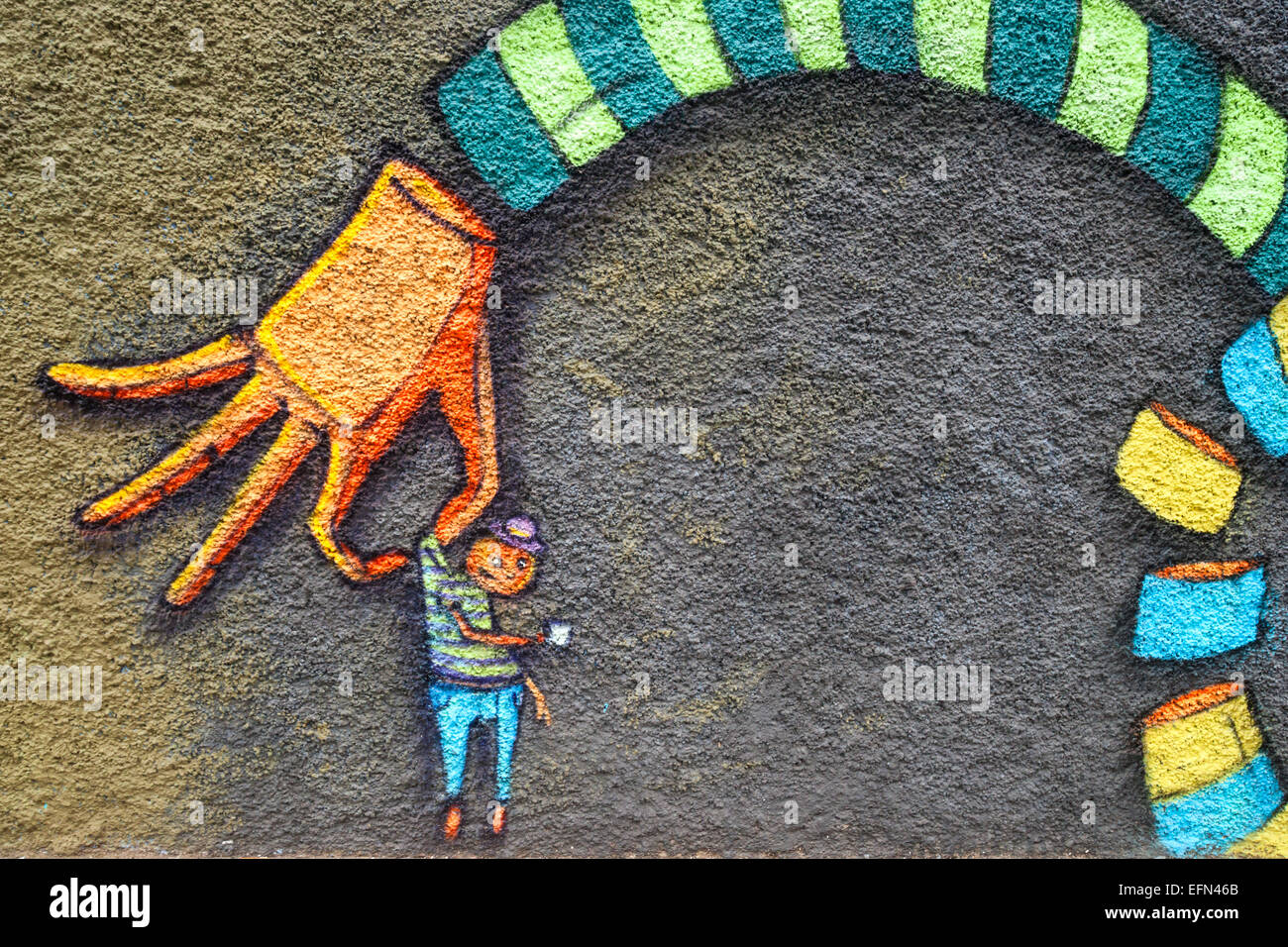Street art mural of hand holding a little boy decorates a building in Valparaiso, Chile, South America - Stock Image