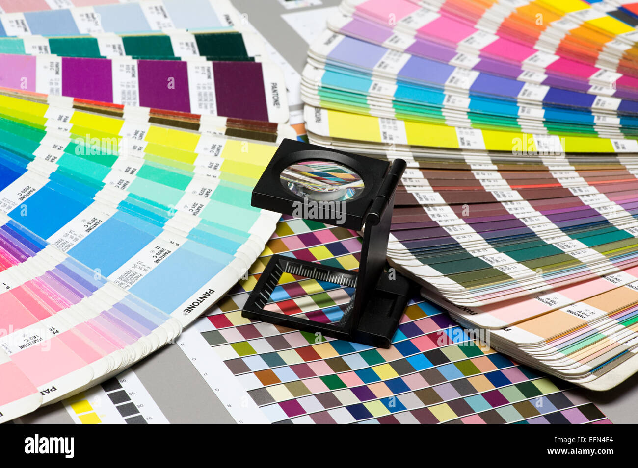Close up Small Magnifying Glass Device on Top of Pantone Color Guide Above the Table. - Stock Image