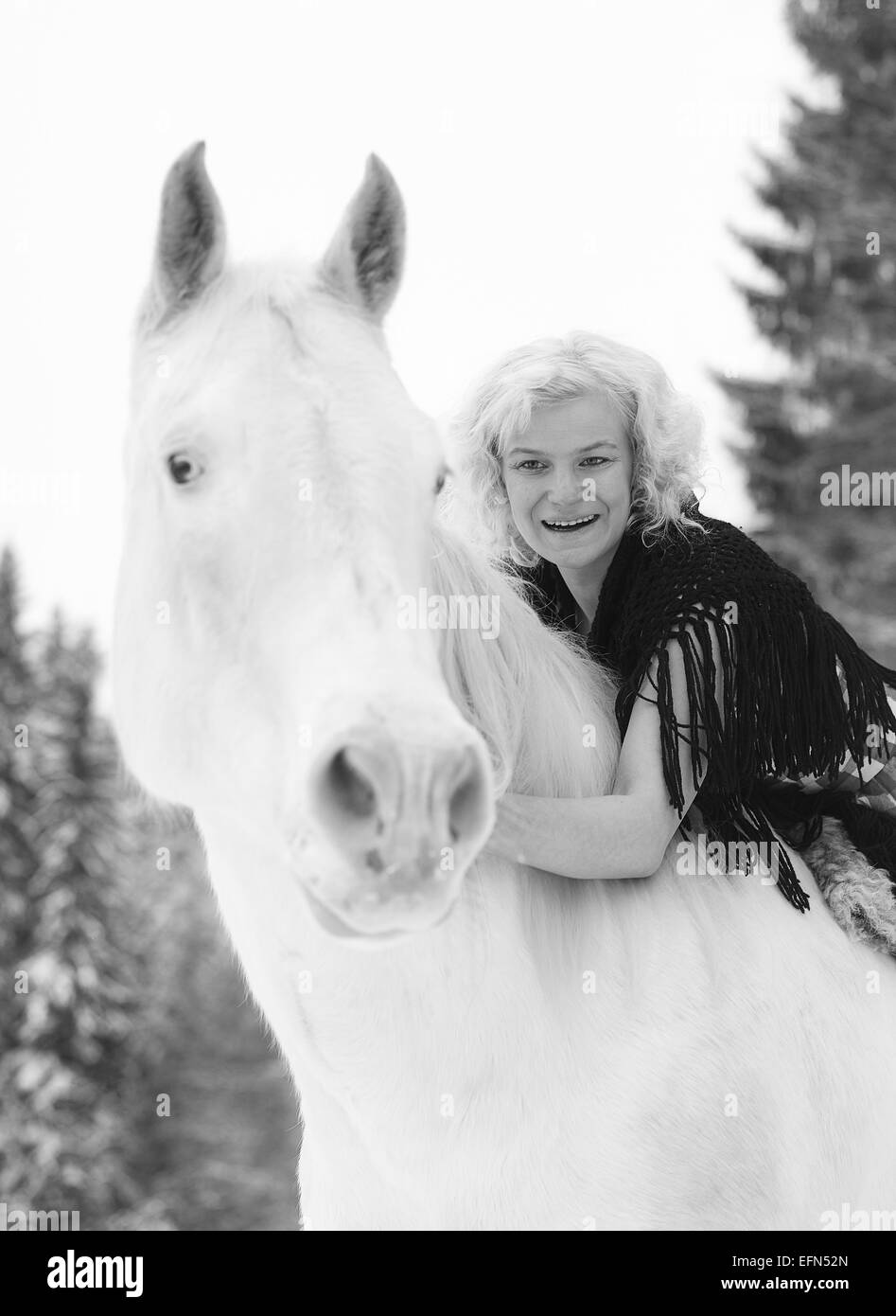 Attractive blond woman hugs a white horse, overcast winter day - Stock Image