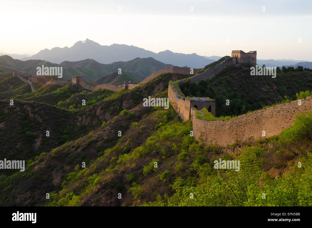The 2,300 year old Great Wall of China is illuminated by the setting sun. - Stock Image