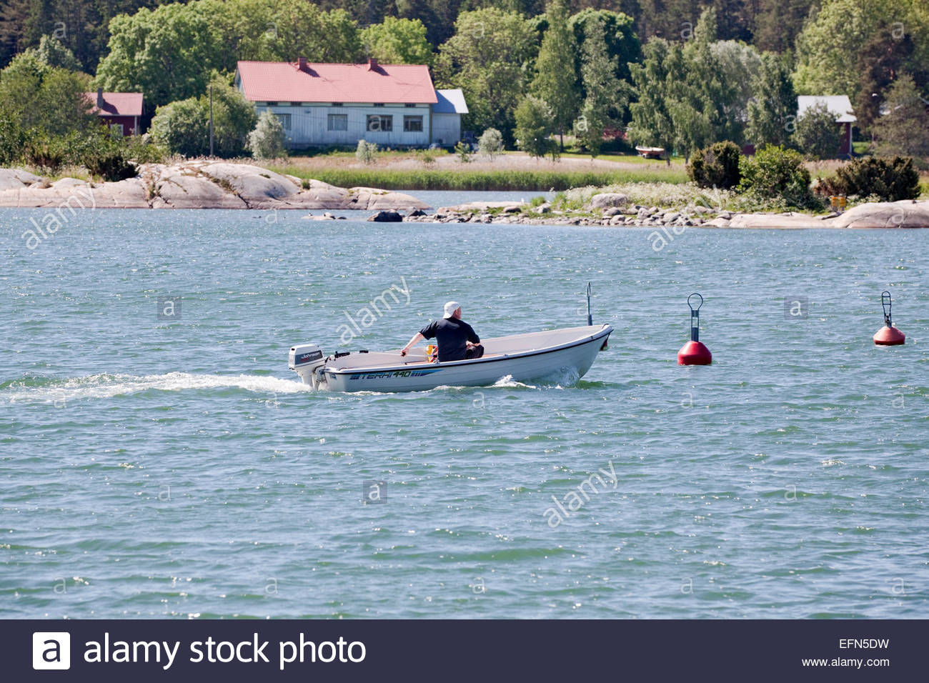 A man in a boat in the archipelago of Turku Finland - Stock Image
