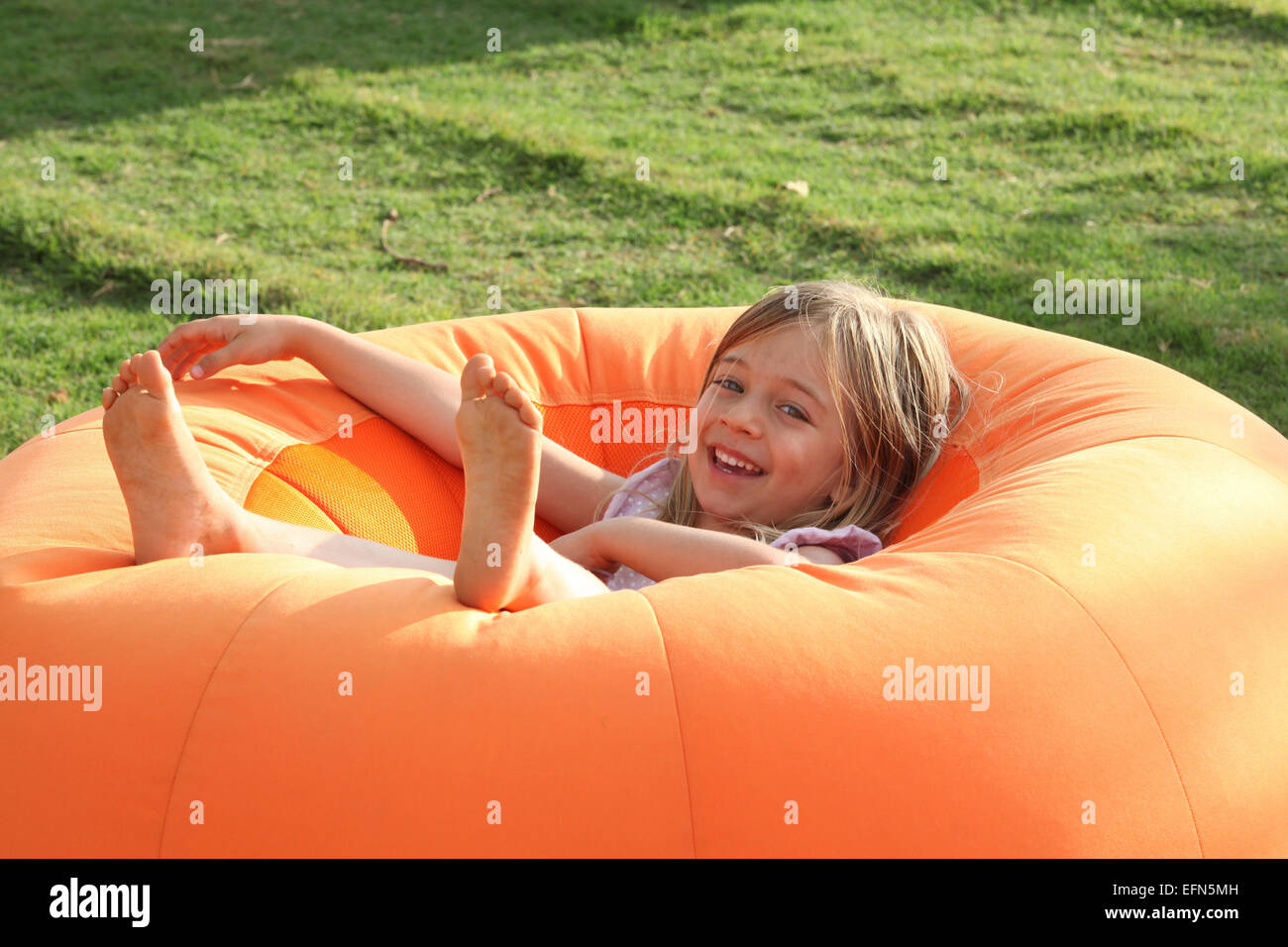 Happy Smiling Young girl on a Bean Bag - Stock Image
