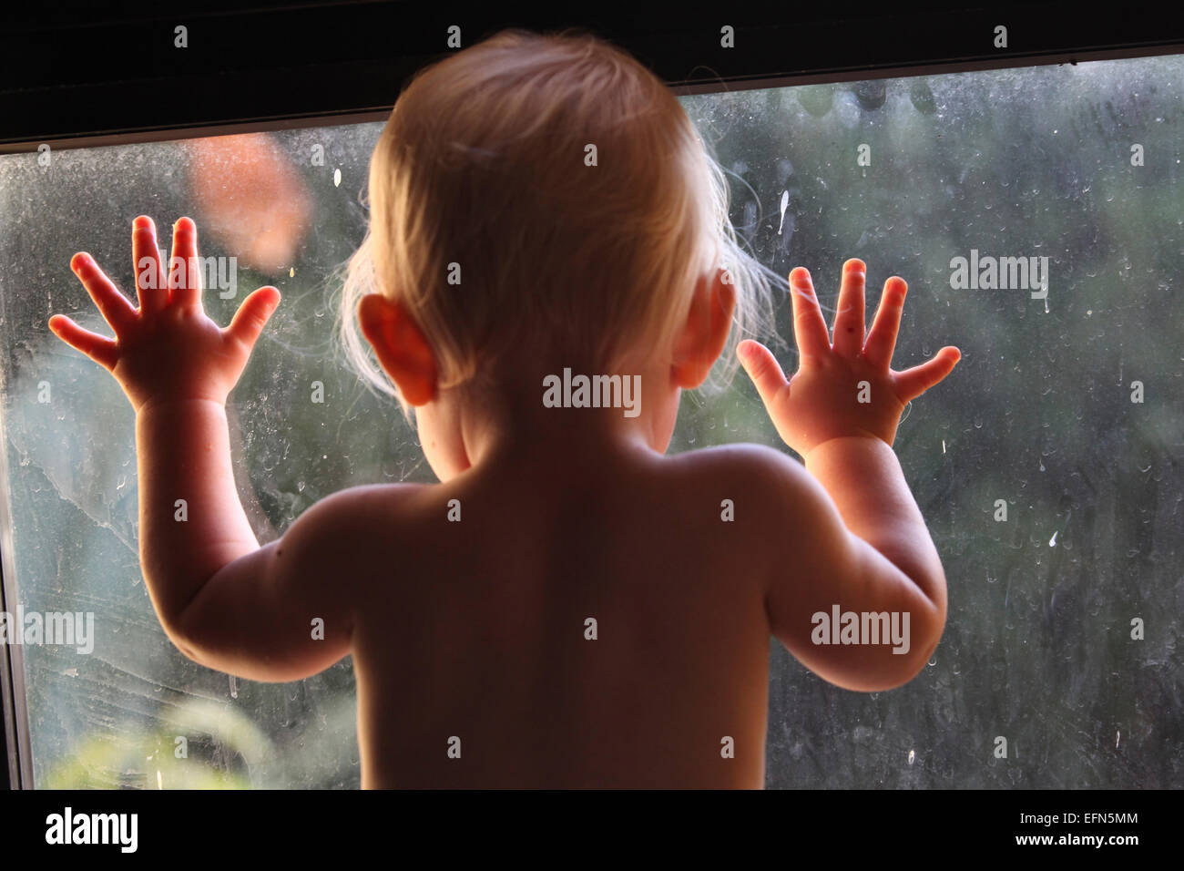 Baby girl looks out through a dirty window - Stock Image