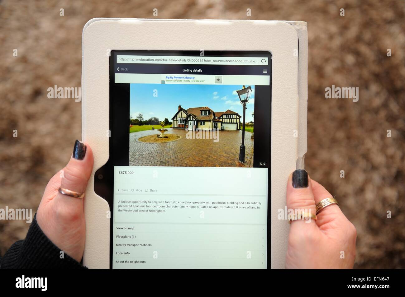 A kindle fire being used to view a house for sale England UK - Stock Image