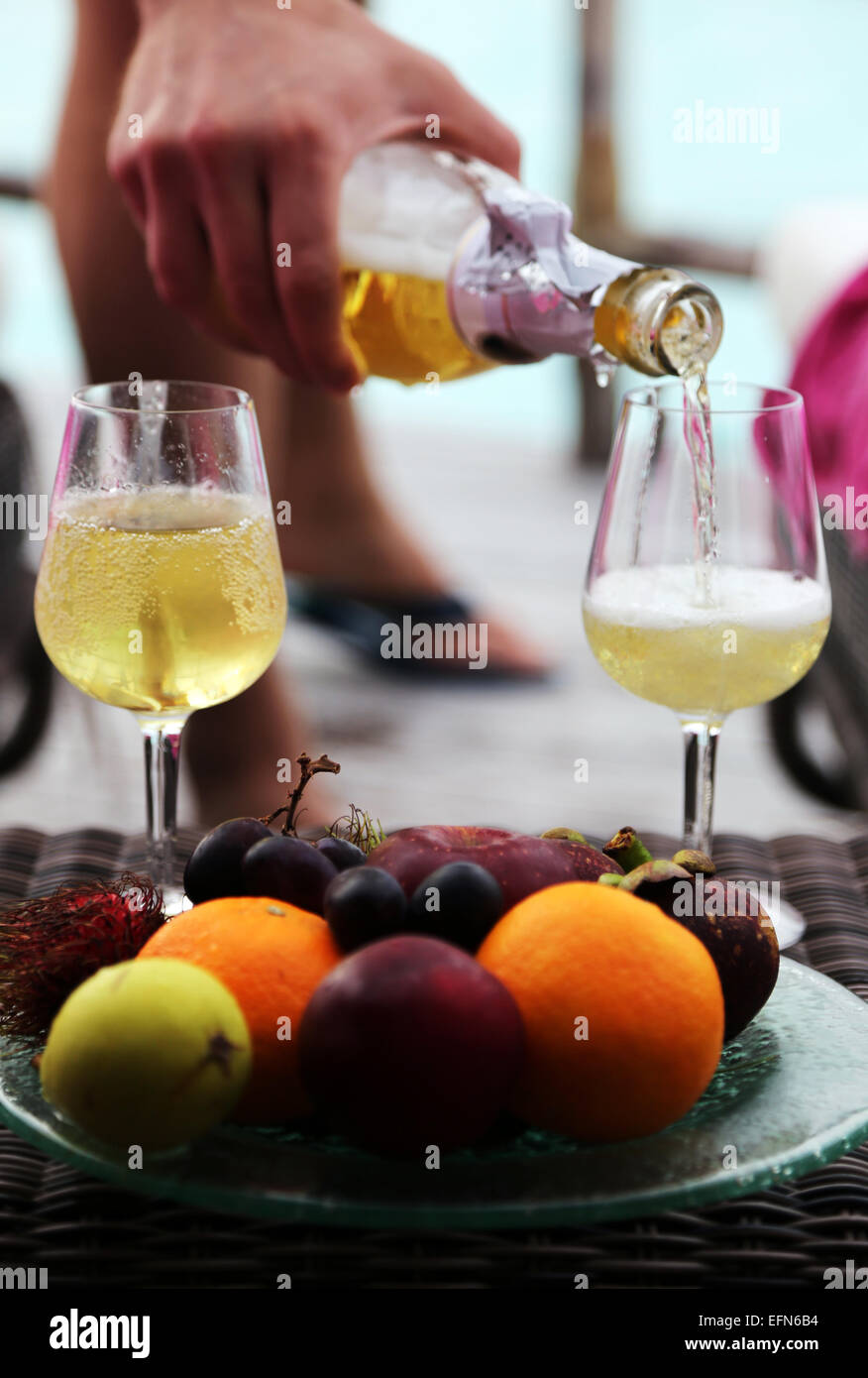 A man's hand pours champagne into two glasses. A plate of exotic fruits is in the front. - Stock Image