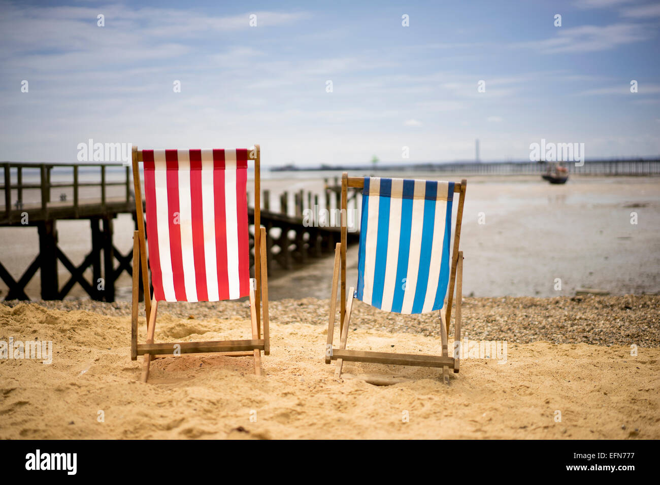 Deck chairs on the beach at Southend on Sea Essex on a bright summer day at low tide - Stock Image