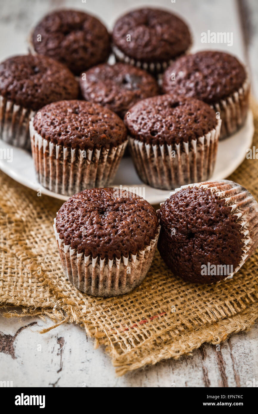 Mini chocolate brownie cupcakes on white wooden background Stock Photo