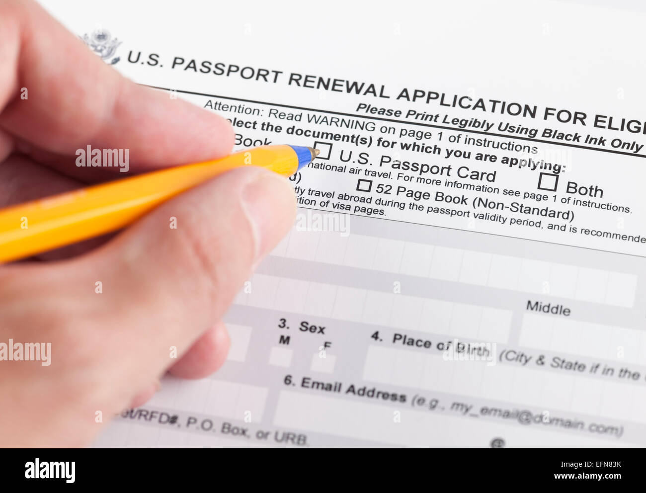 U.S. passport renewal application for eligible individuals and human hand with ballpoint pen. - Stock Image