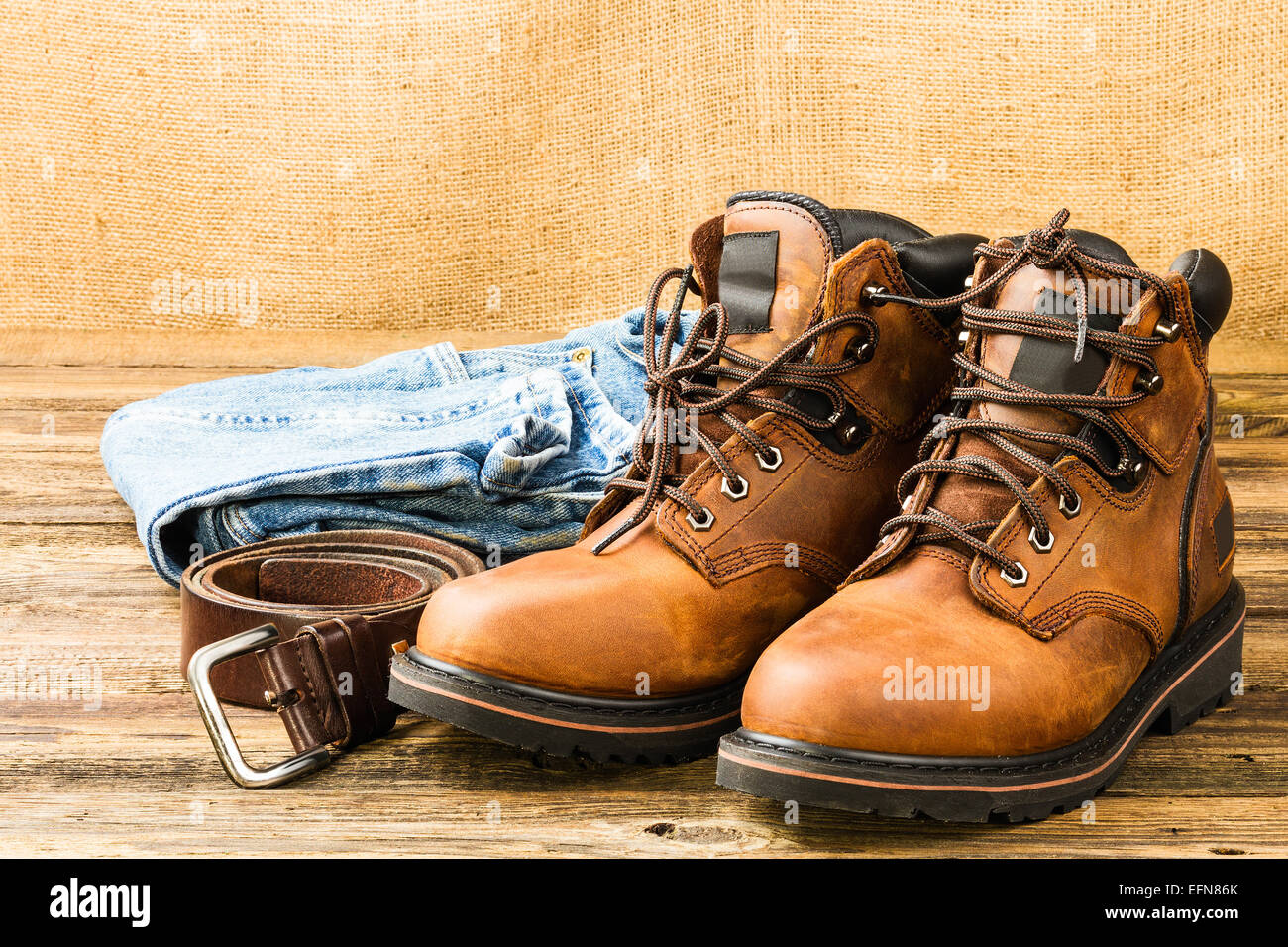 brown men's boots, jeans and belt on wooden background Stock