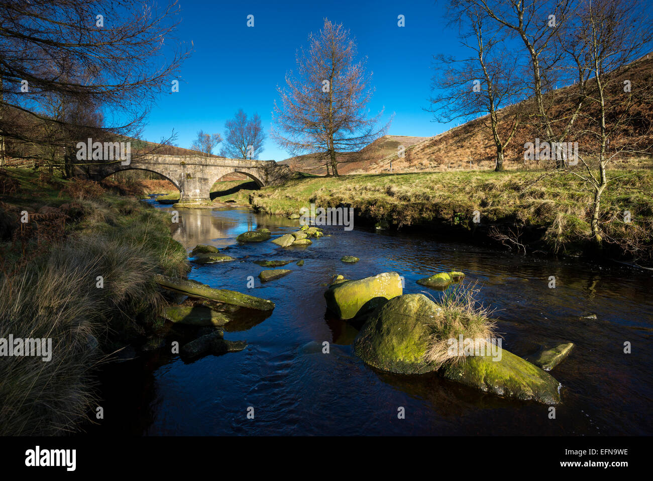 Packhorse bridge at Slippery stones over the river Derwent in the Peak District on a sunny autumn day. - Stock Image