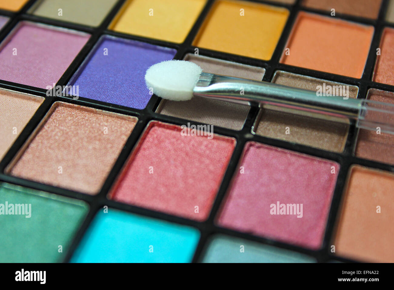 Colorful eyeshadow make up palette. Focus on make up appicator. - Stock Image