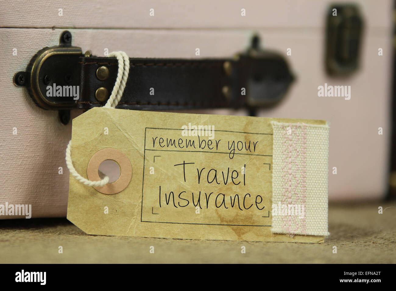 Paper tag with the handwritten words 'remember your travel insurance' on vintage suitcase. - Stock Image