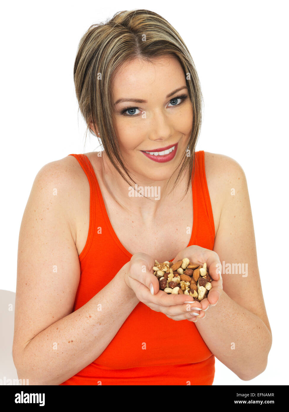 Young Healthy Woman Holding a Handful of Mixed Nuts - Stock Image