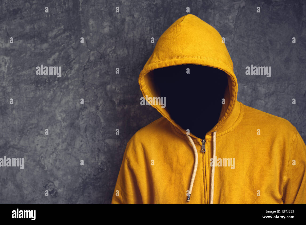 Faceless unknown and unrecognizable person without identity wearing yellow hooded jacket. - Stock Image