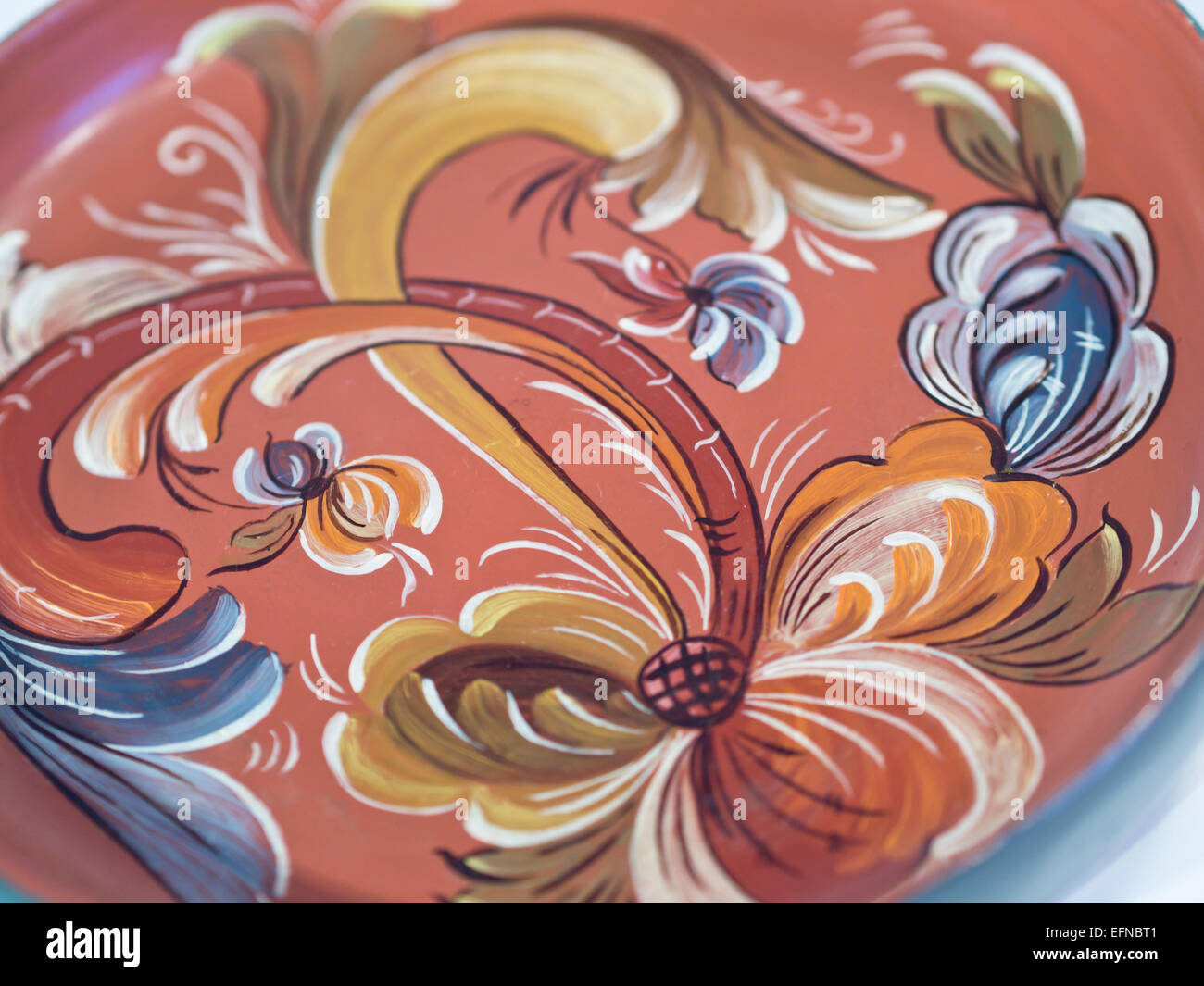 Rosemaling, traditional Norwegian decorative folk art painting, abstracted floral and plant motif on red and blue - Stock Image