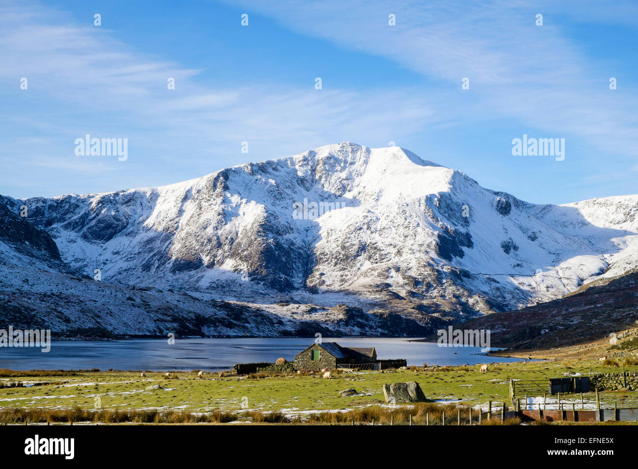 View along Ogwen Valley and lake to Y Garn mountain with snow in winter in mountains of Snowdonia National Park - Stock Image