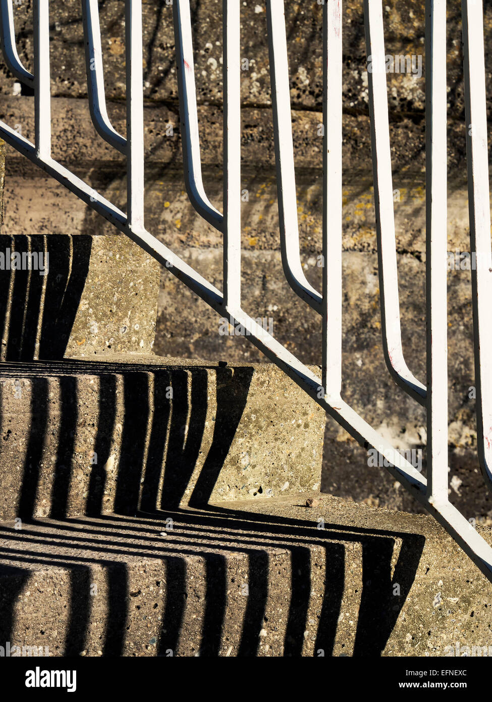 Closeup of concrete stairs with white handrail and black shadow - Stock Image