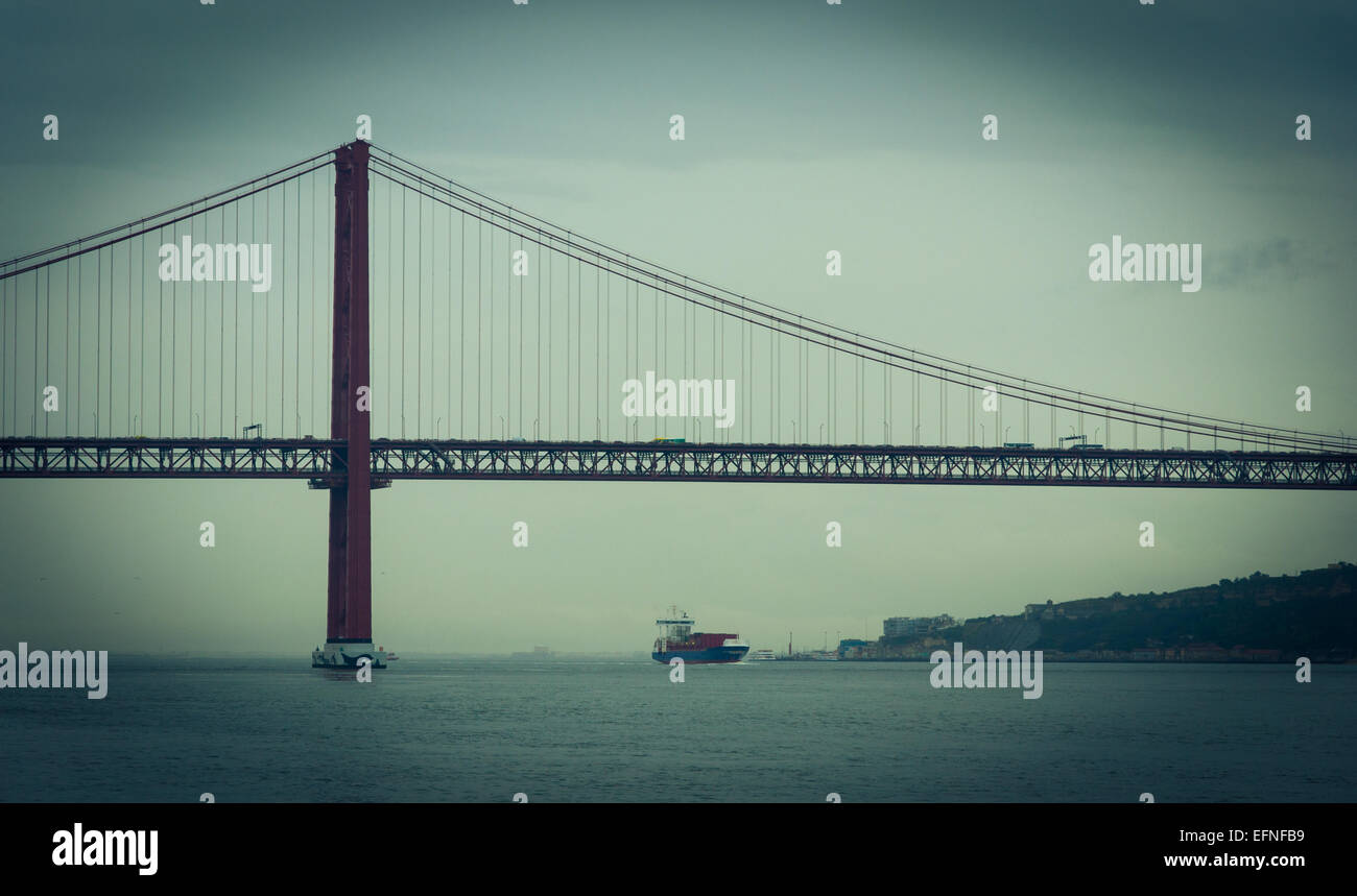 Vignetted photo of Tagus River in Lisbon with a freighter crossing 25 de Abril Bridge Stock Photo