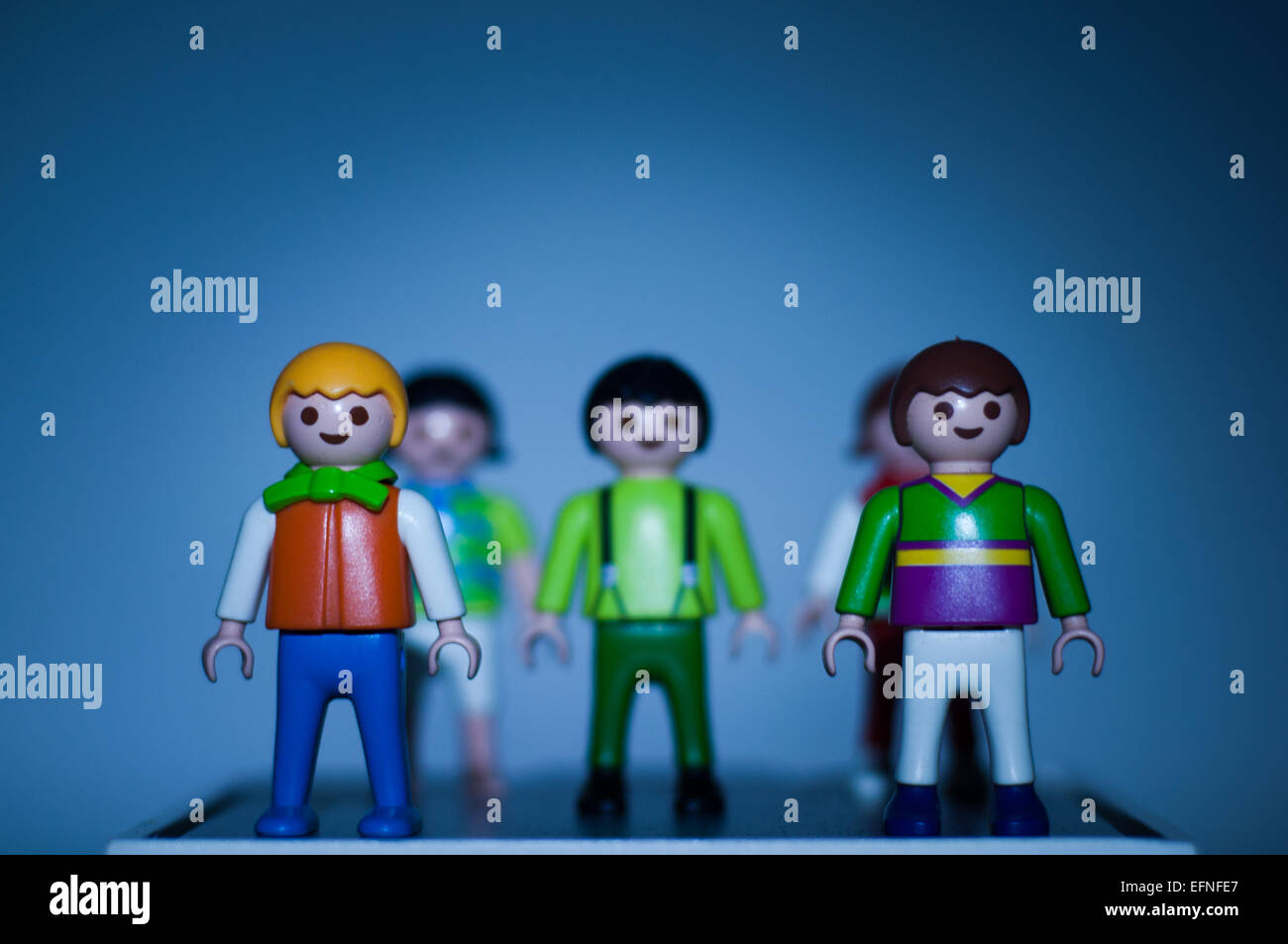 Group of Playmobil toys with a blue background - Stock Image