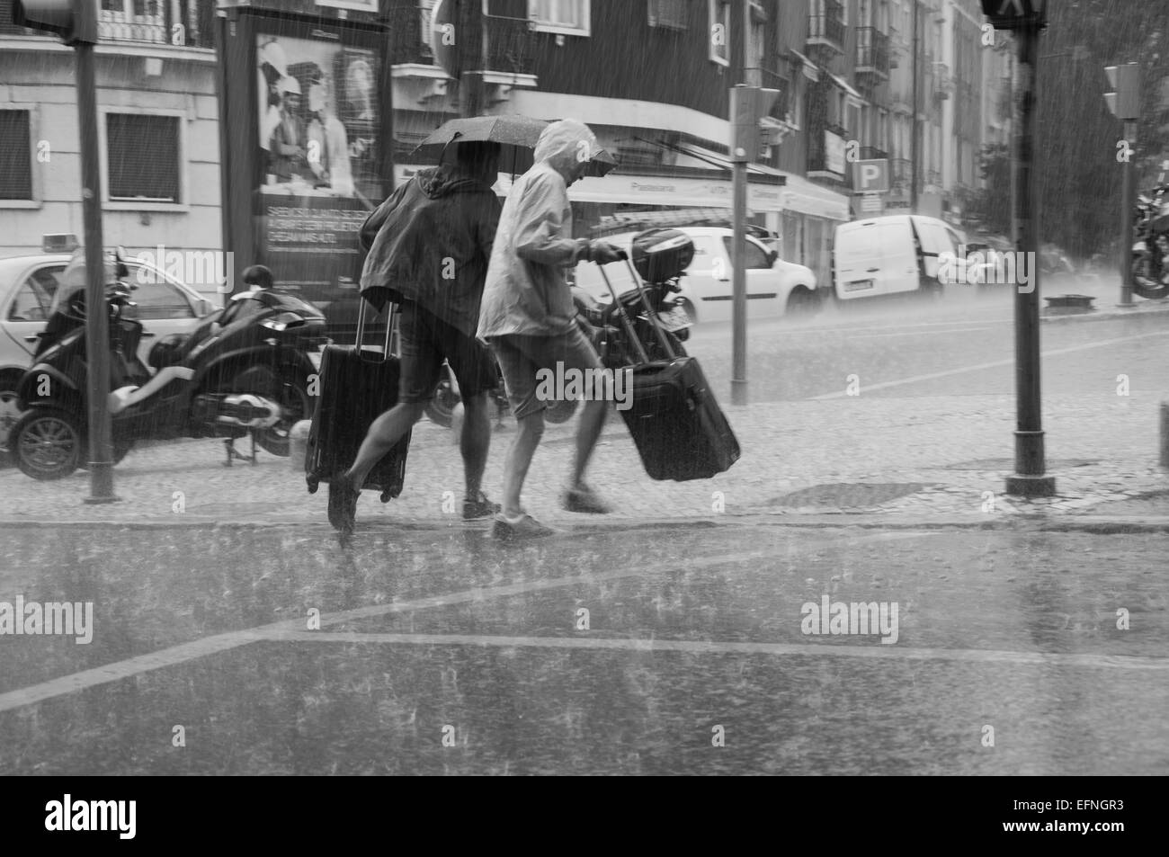 Black and white photo of two people running on the street under heavy rain