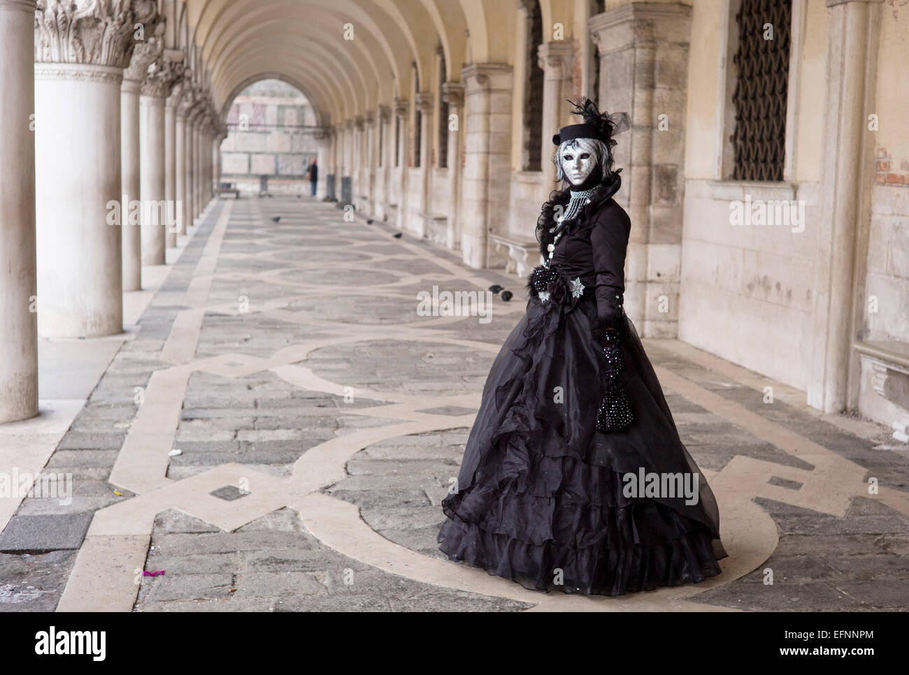 A reveller wearing elaborate costume and mask poses for th camera during the Carnival of Venice, Italy Stock Photo