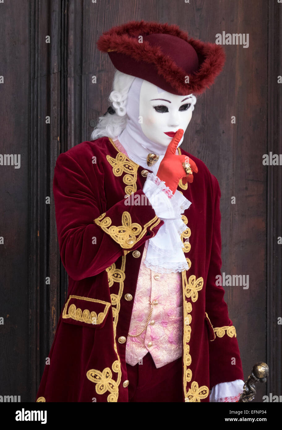 A reveller wearing elaborate costume and mask poses for th camera during the Carnival of Venice, Italy - Stock Image
