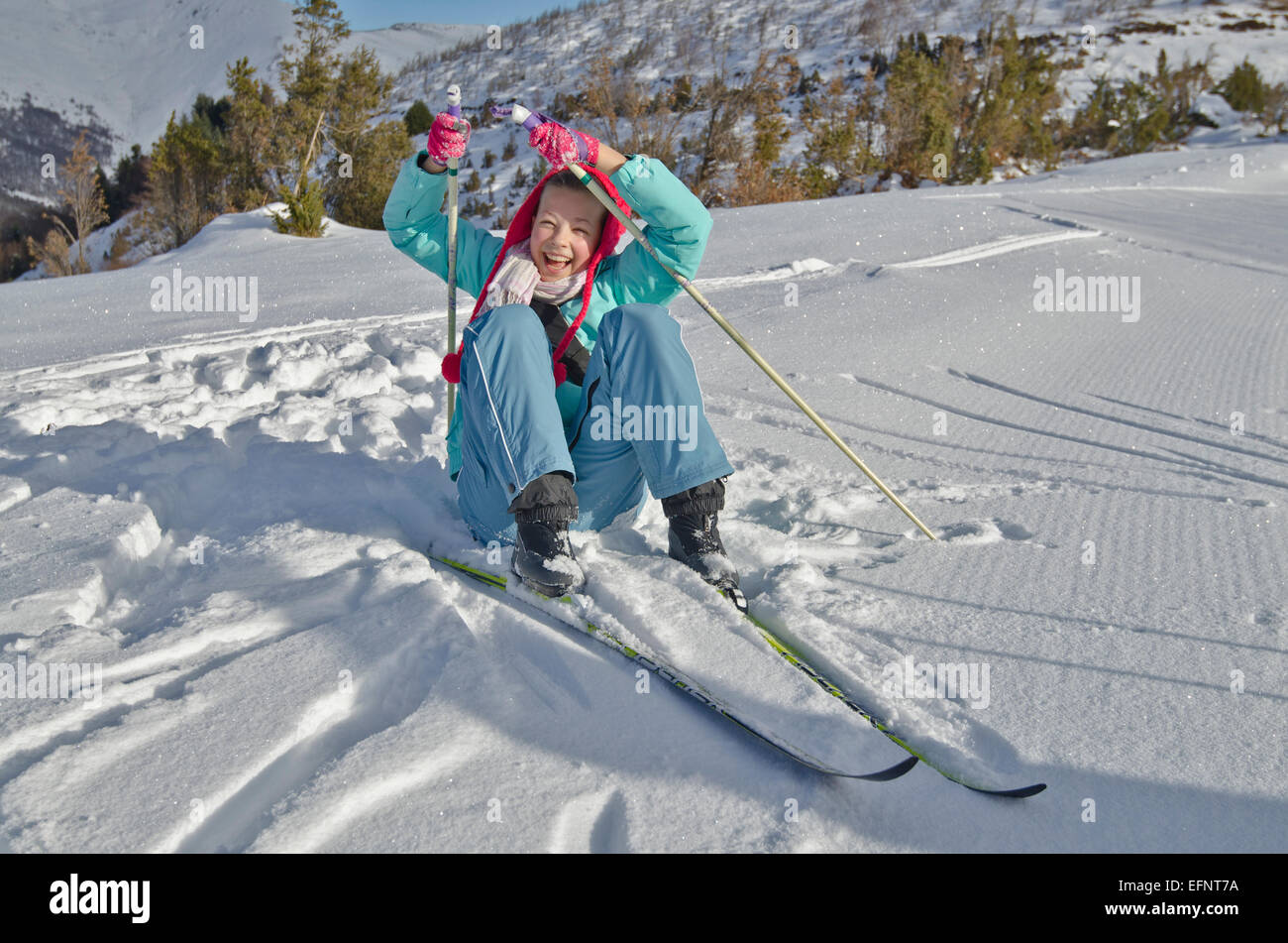 Young girl with red winter hat lifts up after the fall at Nordic ski resort of Valley Azun in High Pyrenees, - Stock Image