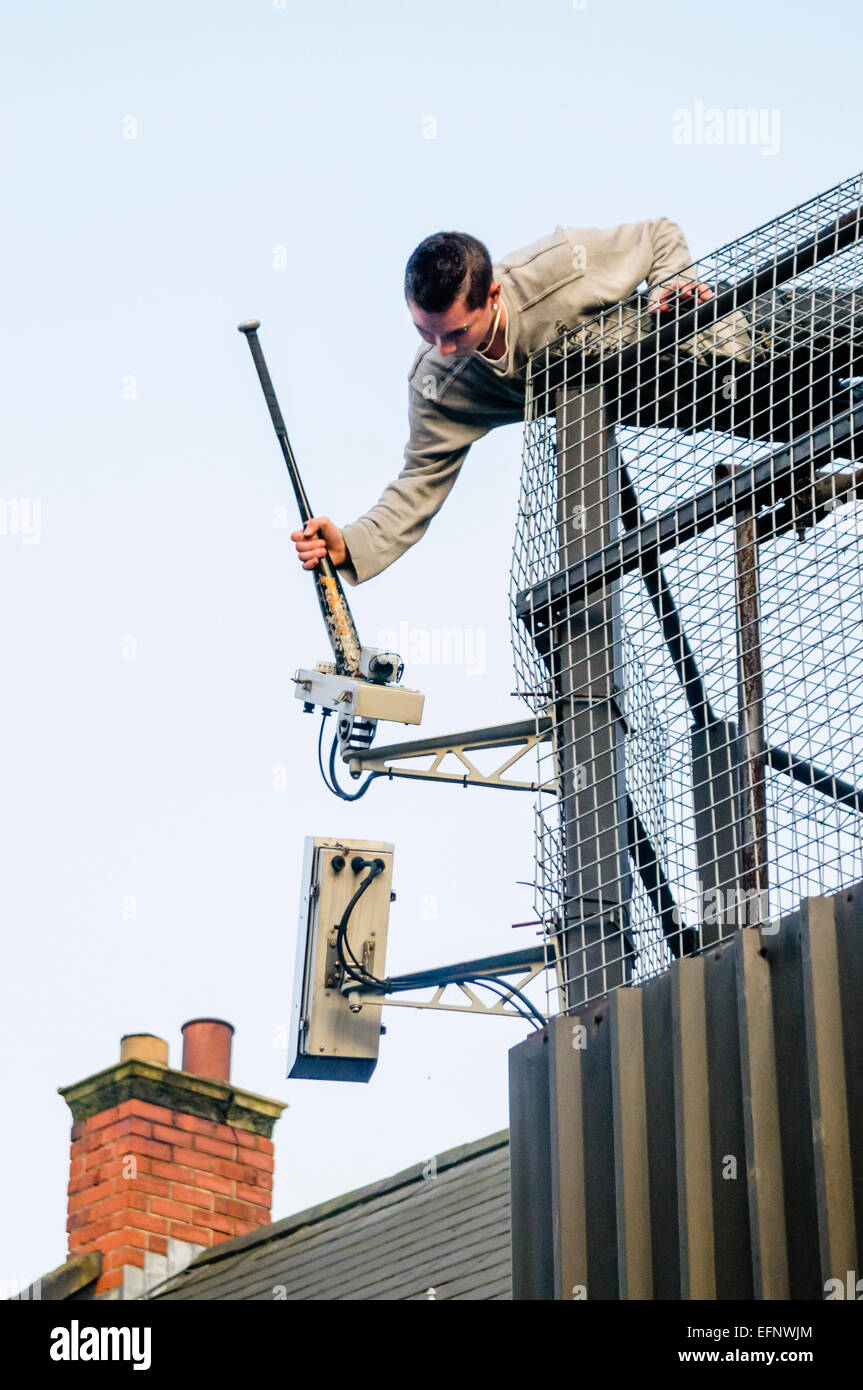 Belfast, Northern Ireland. 31 Aug 2009 - A youth uses a baseball bat to destroy a CCTV camera at a decommissioned - Stock Image