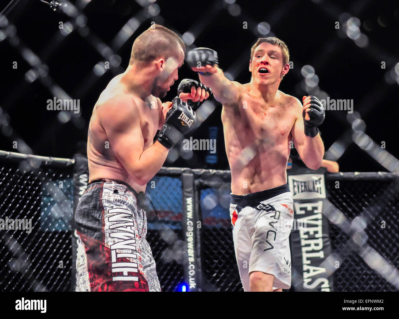 MMA fighter throws a punch to his opponent. Stock Photo