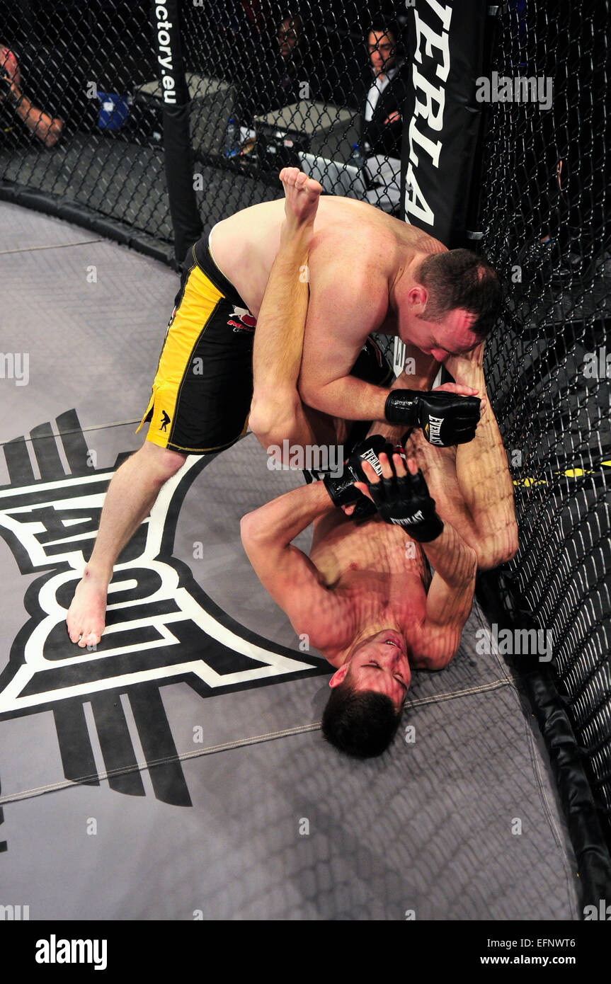 MMA fighter holds his opponent on the canvas and lands punches to his head. - Stock Image