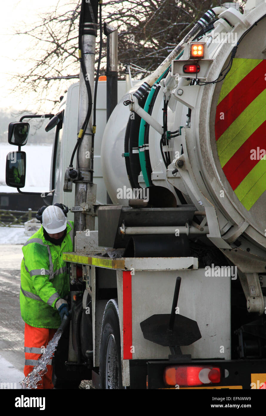 Surface water is normally drained off roads by gullies and grips. Gully tanker at work 2 operatives men at work. - Stock Image