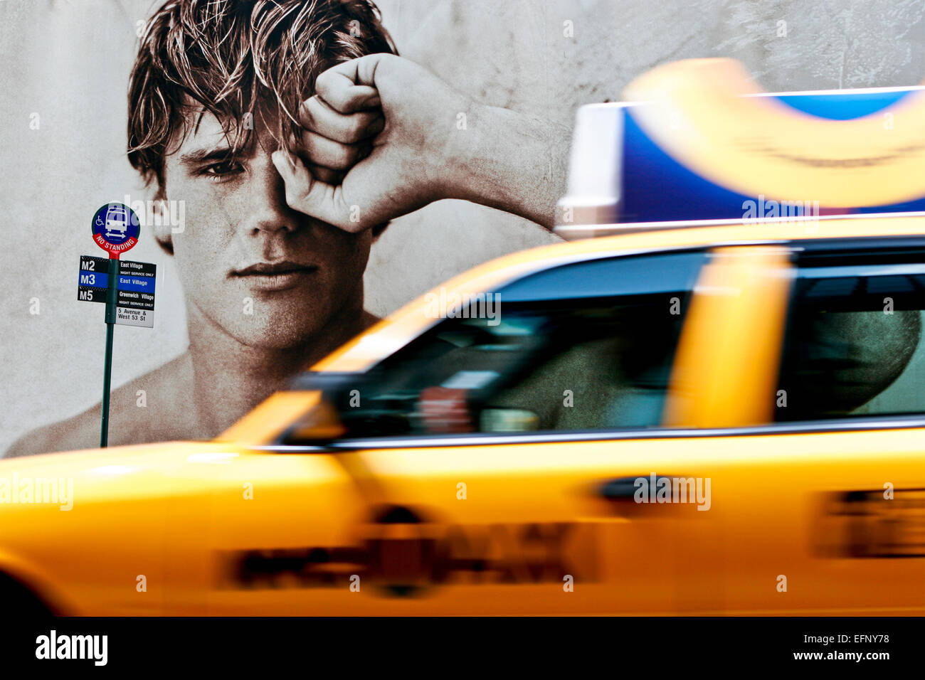 Handsome young male model on fashion advertising billboards at bus stop, yellow cab taxi motion blur passing. 5th - Stock Image