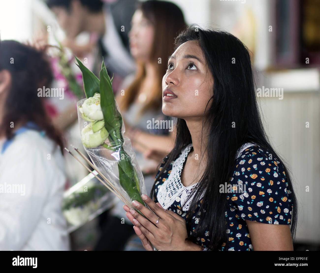 Young Asian woman fervently praying in a Buddhist monastery - Stock Image