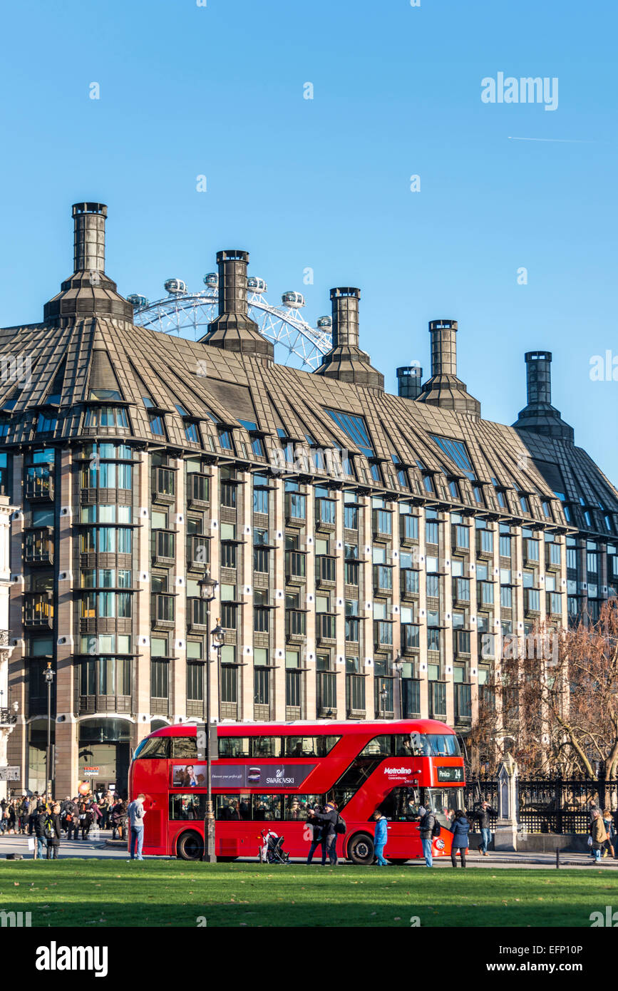 A London Red Bus is seen across Parliament Square, behind which is Portcullis House and the London Eye - Stock Image