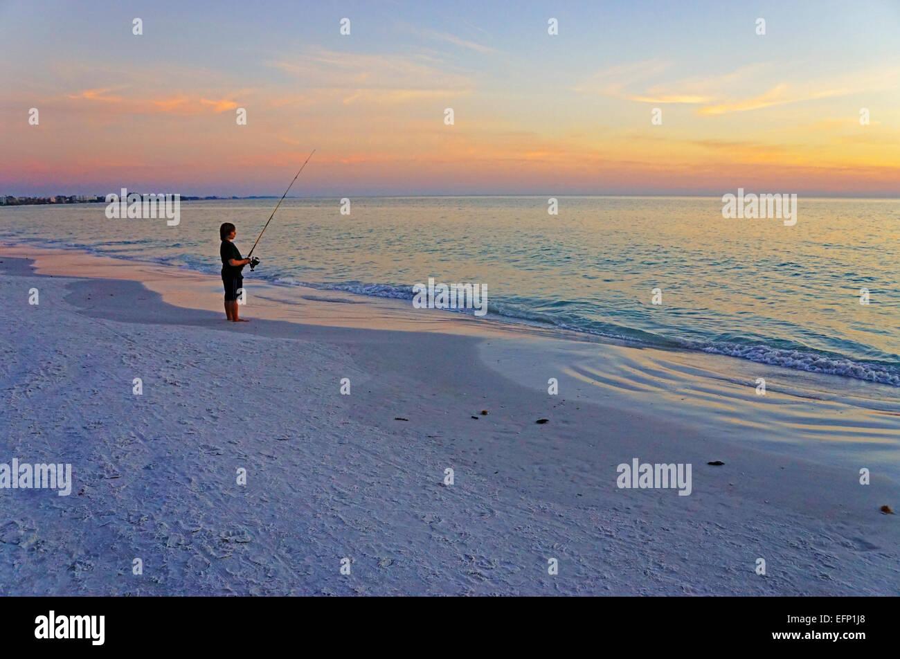 Boy fishing at sunset on Siesta Key Beach at Sarasota, Florida. - Stock Image