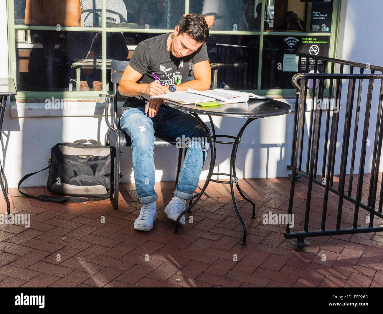 A twenty something male college student studies at a table on a patio outside a coffee shop in Santa Barbara, California. - Stock Image