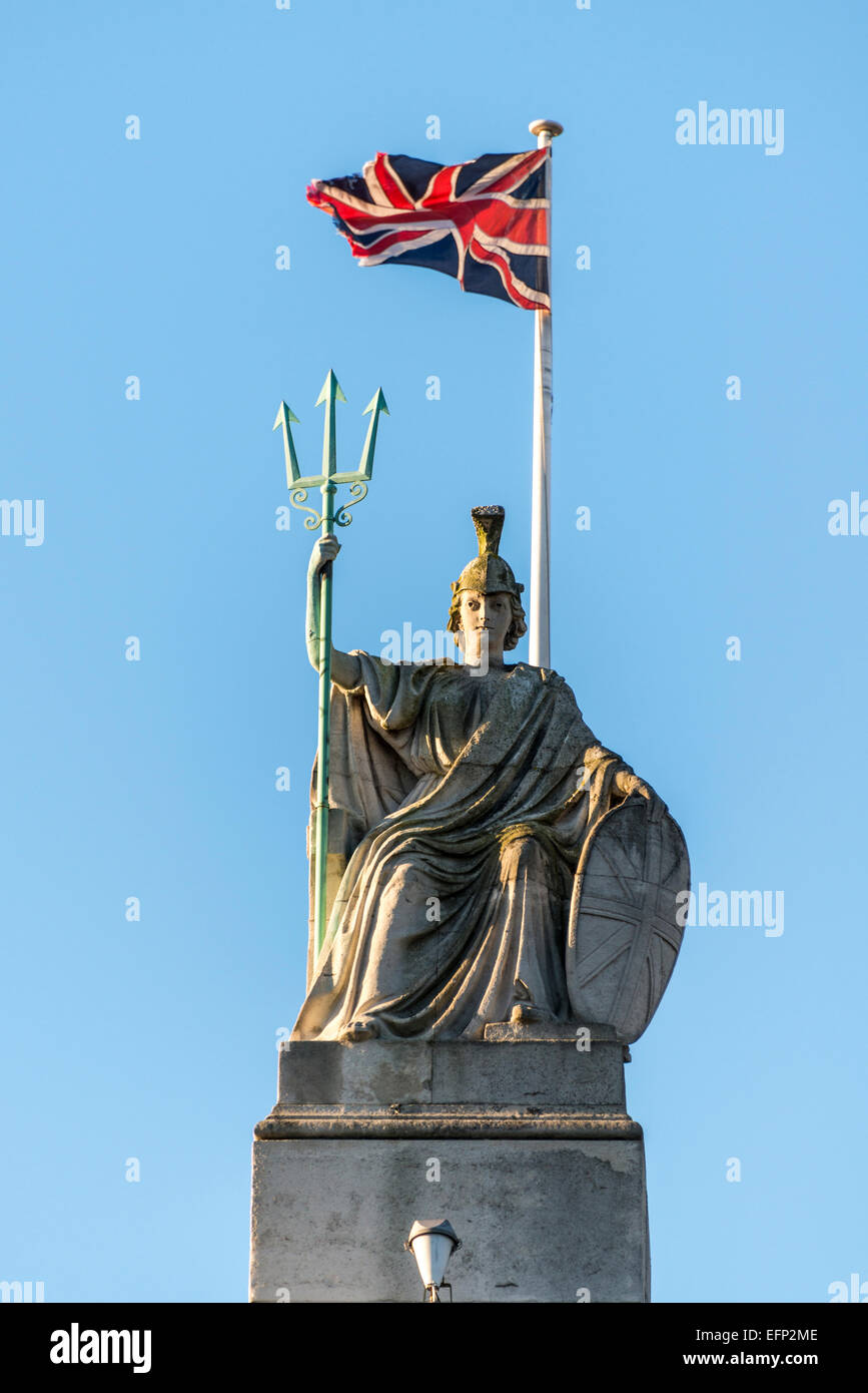 The Union Jack flag of the United Kingdom flies behind a statue of Britannia located on the roof of Tate Britain. - Stock Image