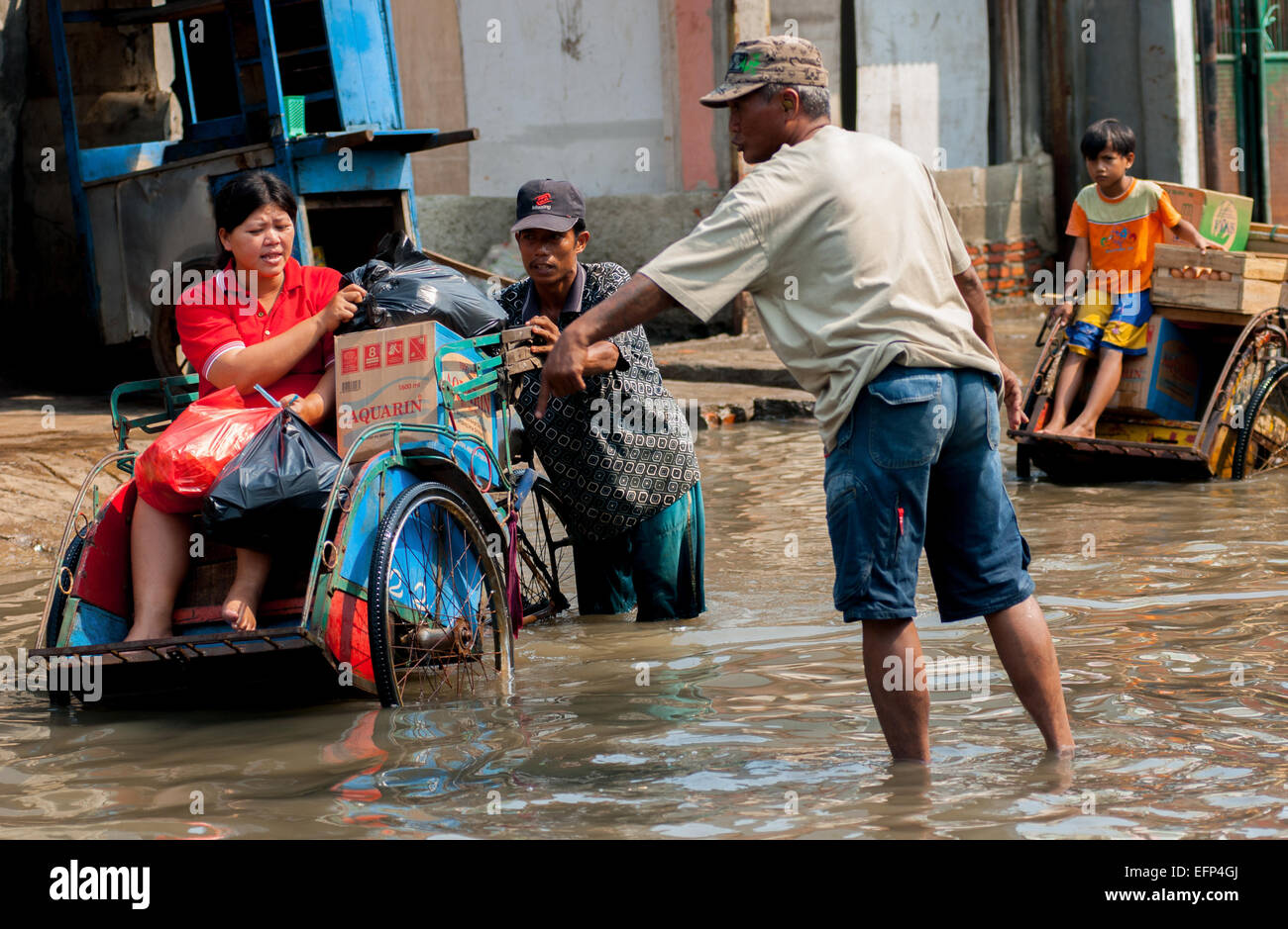 Northern Jakarta city residents passing through sea tides in Muara Baru, North Jakarta. - Stock Image