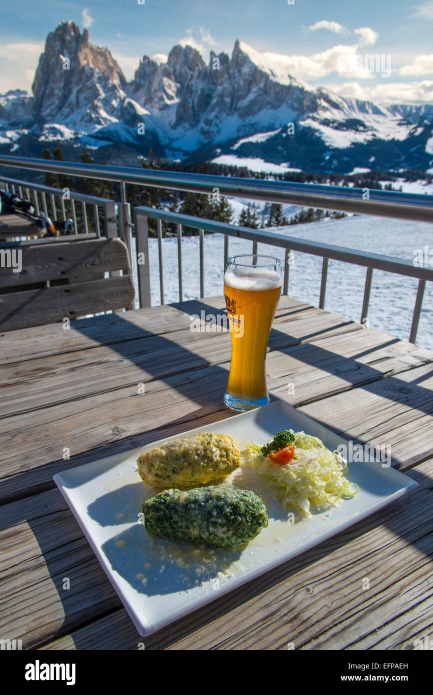 Traditional canederli or knodel plate served on the table with view over the snowy Dolomites, Alto Adige, South - Stock Image