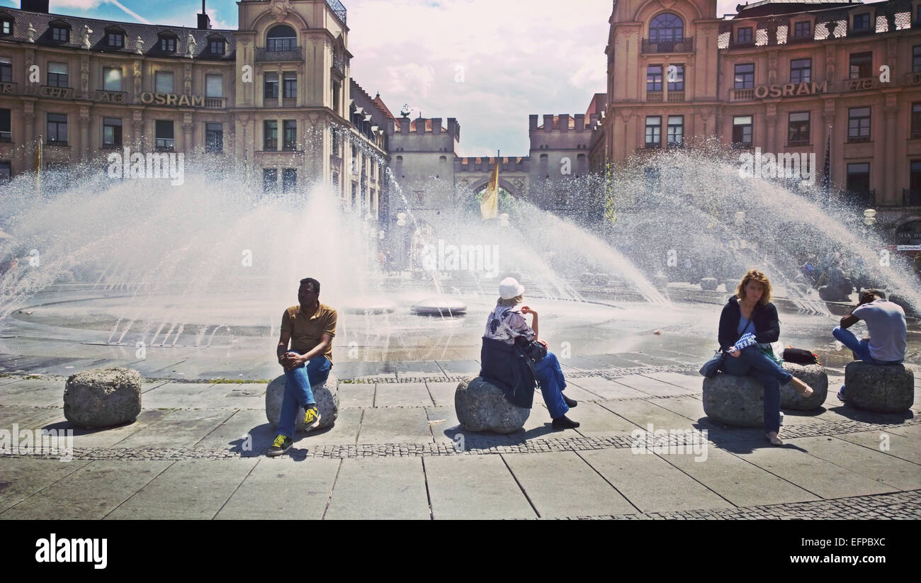 MUNICH, GERMANY hot weather in Munich, more than 30 Celsius, people look for refreshment near the fountain at Karplatz - Stock Image